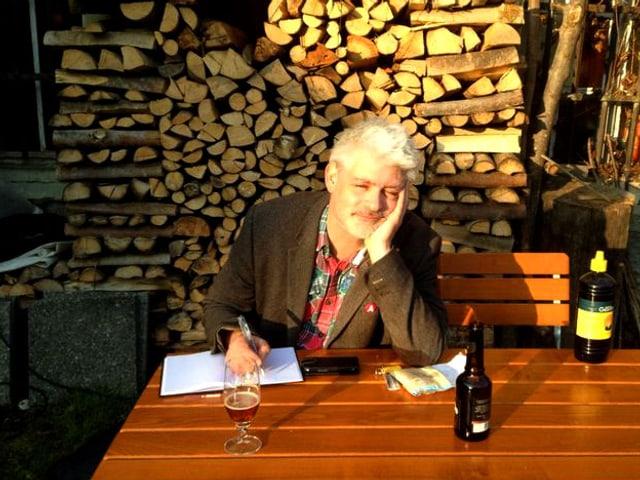 Mann sitzt an Tisch und drinkt.