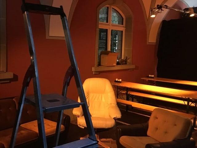 dunkler Raum mit Bänken und zwei Polsterstühlen und Leiter
