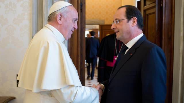 Der Papst und Hollande geben sich die Hand.
