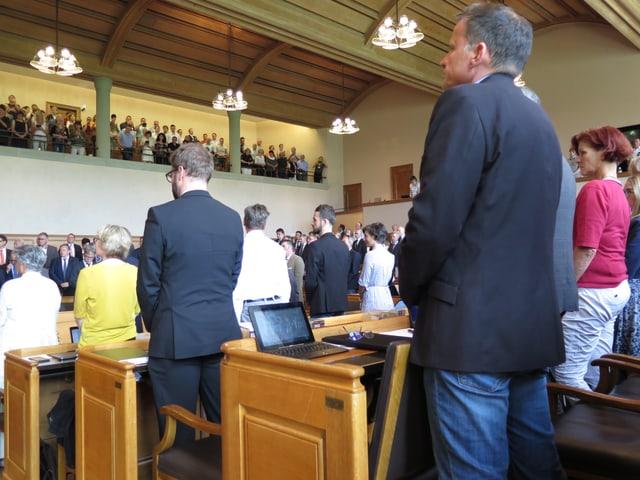 Stehende Parlamentarierinnen und Parlamentarier und Publikum