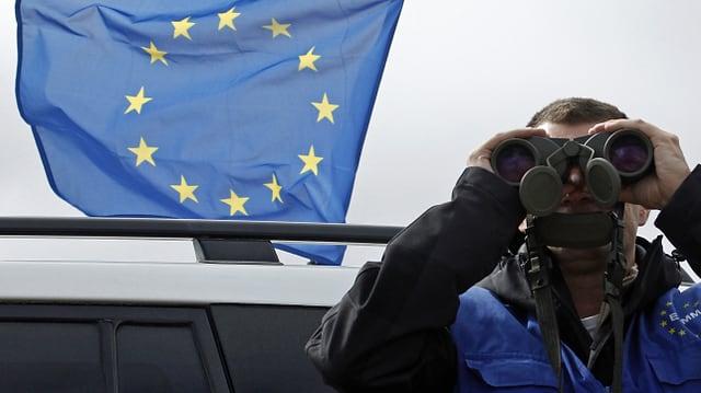 Ein Beobachter der EU schaut durch Ferngläsern aufs Meer hinaus. (reuters)