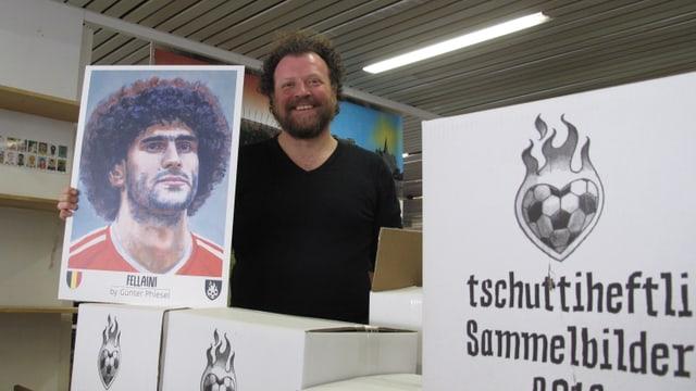 Tschuttiheftli-Projektleiter Silvan Glanzmann mit den Schachteln voller neuer Fussball-Bildli.