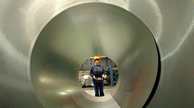 Frau mit gelbem Sicherheitshelm blickt in Verzinkte grosse Röhre.