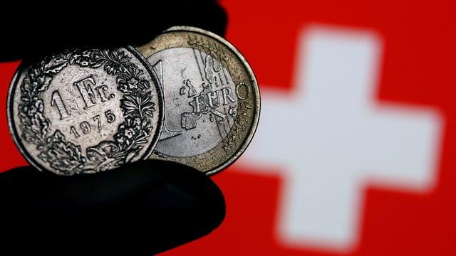 1-Franken-Müne und 1 Euro zwischen Daumen und Zeigefinger vor ein Schweizerkreuz gehaten