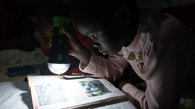 Kind mit Taschenlampe über einem Schulbuch