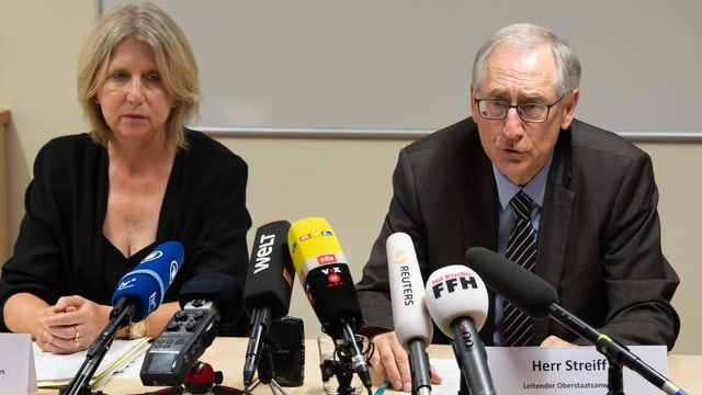 Zwei Personen vor Mikrofonen.