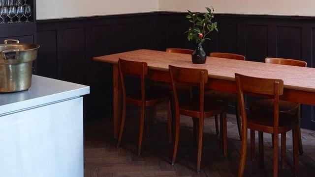 Blick auf einen langen, ungedeckten Holztisch mit einer Blumvase drauf im Restaurant Gamper.