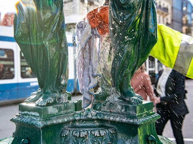 Person reinigt einen kleinen Brunnen