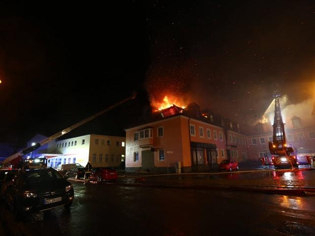 Die Feuerwehr löscht die brennende Flüchtlingsunterkunft in Bautzen.