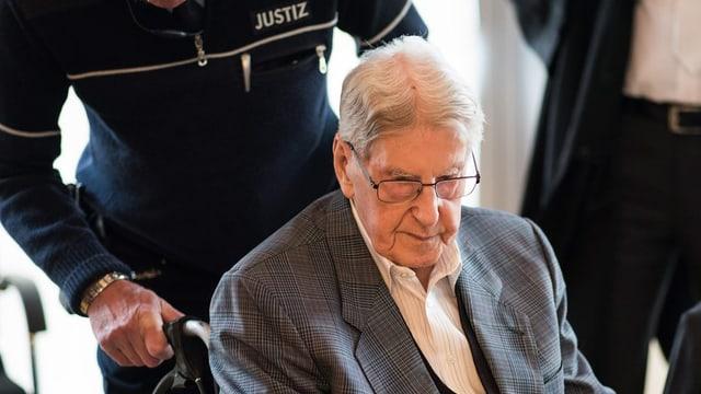 Der Angeklagte Reinhold Hanning wird im Rollstuhl an seinen Platz geschoben.