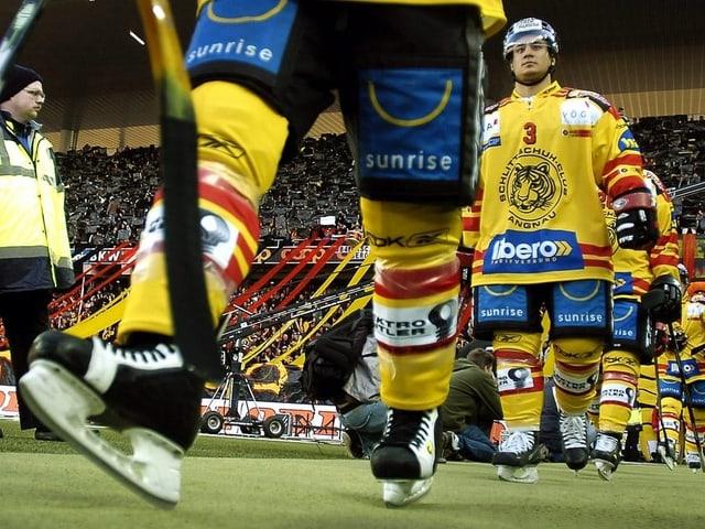 Die Spieler laufen über den Kunstrasen mit ihren Schlittschuhen Richtung Eisfeld.