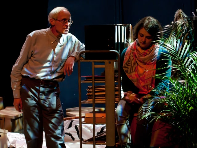 Martin Vosseler steht auf der Theaterbühne. Aninna Poliva sitzt auf einem Stuhl, inmitten von Bühnenrequisiten.
