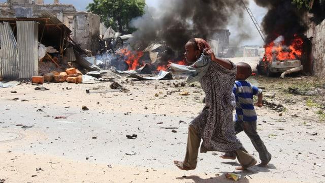Im Vordergrund rennen zwei Kinder, im Hintergrund brennen Autos