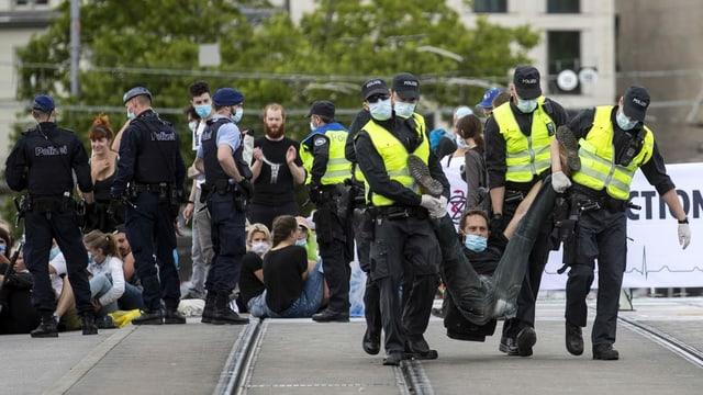 Purtret da policists che portan davent ils demonstrants e las demonstrantas.