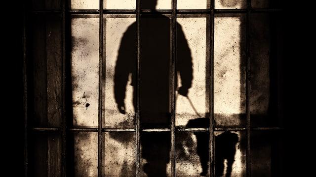 Eine dunkle Männergestalt hinter Gittern