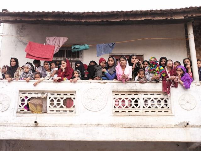 Frauen und Mädchen mit Kopftüchern drängen sich auf einem Balkon.