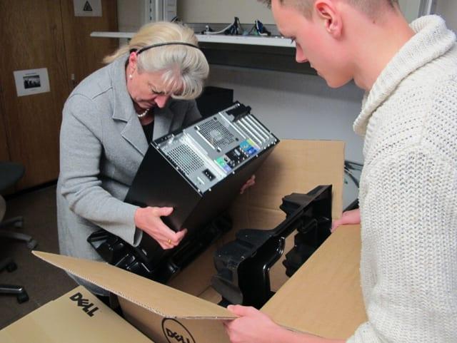 Barbara Janom hievt einen Computer aus einer Kartonschachtel