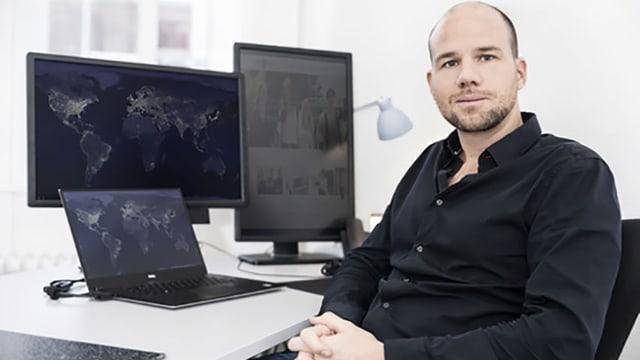 Martin Schröder in schwarzem Hemd vor seinem Schreibtisch sitzend