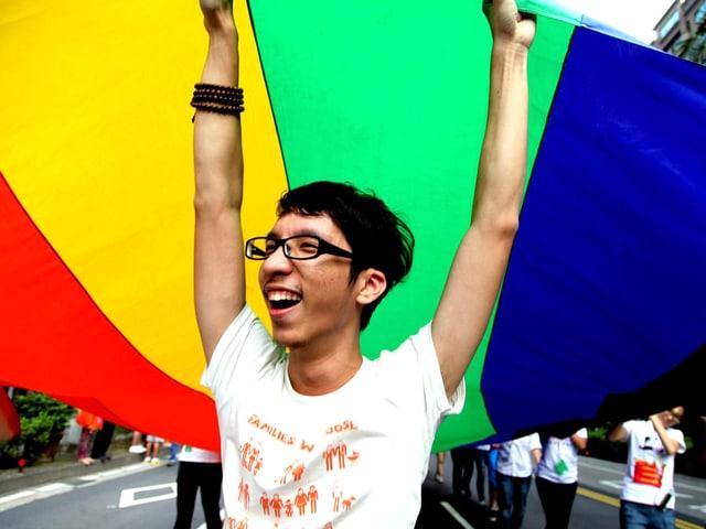 Ein junger Mann hält den Anfang einer meterlangen regenbogenfarbenen Fahne in die Luft.