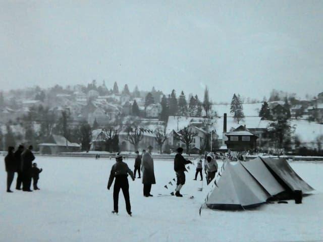 Menschen stehen auf dem Eis um Zelte herum.