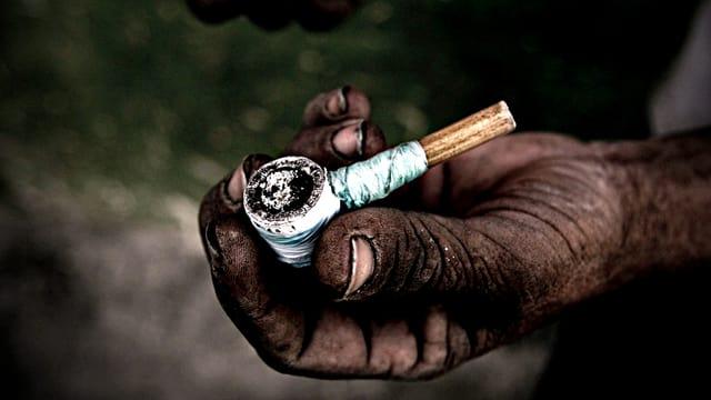 Eine Hand, schwarz vor Dreck, hält eine selbstgebastelte, kleine Pfeife, in der Paco geraucht wird.