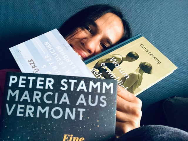 Annette König vor einer blauen Tabetenwand mit drei Sammelbänden mit Short Stories.
