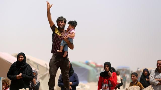 Menschen stehen in einem staubigen Zeltlager, ein bärtiger Mann mit Kind auf dem Arm gestikuliert und scheint etwas zu rufen.