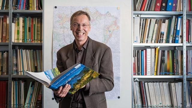 Raimund Rodewald steht mit einem Buch in seinem Büro.