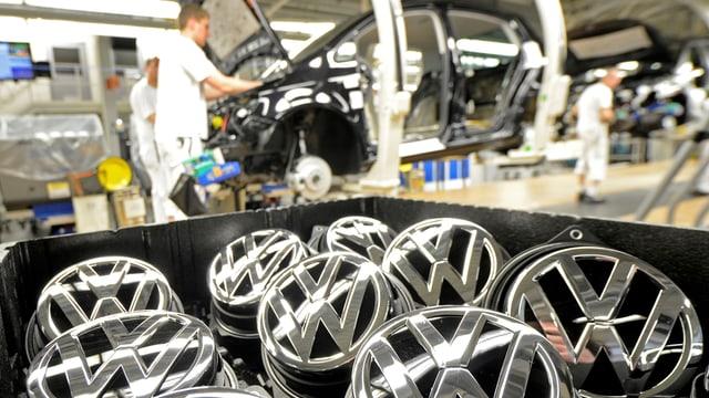 Symbolbild: VW-Markensymbole werden in der Produktionsstrasse eingebaut.