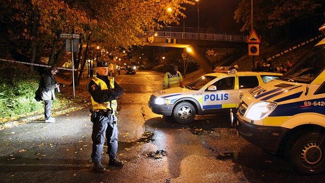 Polizist steht in der Nacht vor mehreren Streifenwagen. Archivbild