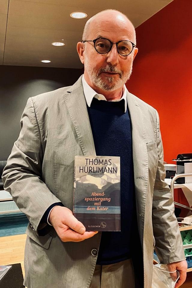 Mann mit Glatze und Brille hält Buch in der Hand