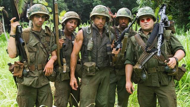 Eine Gruppe von Männern im Dschungel. Sie sind in Militäruniformen gekleidet und tragen schwere Waffen.