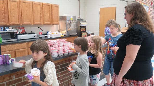 Schüler an der Essenstheke, eine Lehrerin schaut zu.
