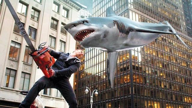 Ein Mann schwingt eine grosse Kettensäge gegen einen heranfliegenden Riesenhai.