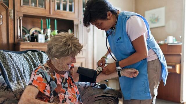 Eine Pflegerin misst den Blutdruck einer älteren Frau