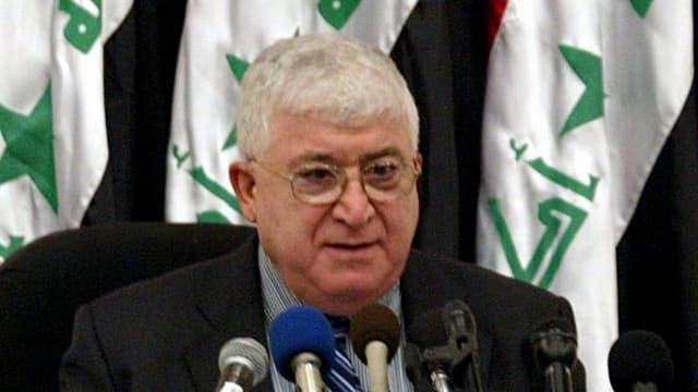 Fuad Massum steht vor irakischen Flaggen an einem Rednerpult