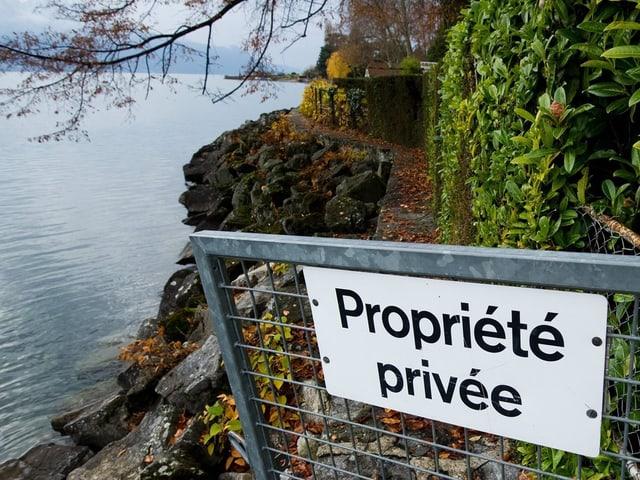 Ein Schild mit der Aufschrift «Privates Eigentum», dahinter ein schmaler Weg entlang des Ufers
