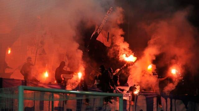 Fussballfans brennen im Stadion rote Pyrofackeln ab.
