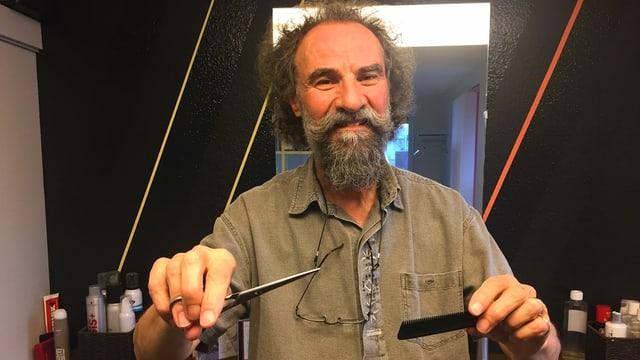 Coiffeur Robert Meierhofer hat eine Schere und einen Kamm in den Händen