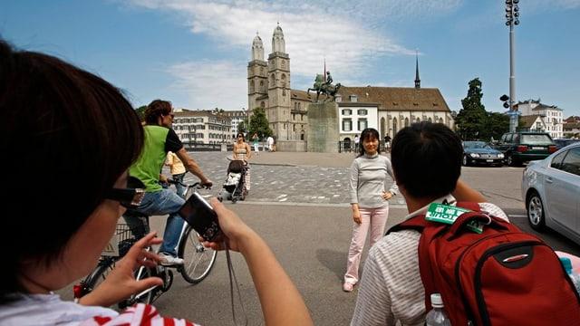 Touristen aus Asien posieren vor dem Denkmal von Hans Waldmann in Zürich