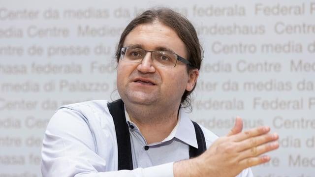 Jörg Mäder trägt eine Brille und hat lange Haare, die er hinten zusammengebunden hat. Bild von einer Pressekonferenz im Dezember 2020.