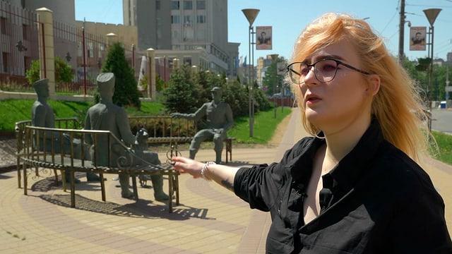 Frau in schwarzer Bluse zeigt auf Statue aus Bronze hinter sich