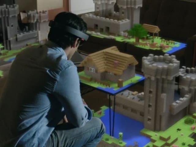 Mann sitzt vor einem Tisch, darauf ein virtuelles Schloss aus Bausteinen.
