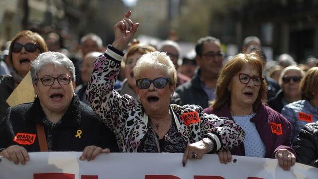 Drei ältere Frauen - zwei mit kurzen grauen Haaren, eine mit längeren braunen - an einer Demonstration. Sie halten ein Transparent und skandieren Parolen.