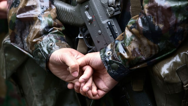 Hände eines Soldaten, der sie hinter seinem Rücken hält. Darunter ist seine Waffe.