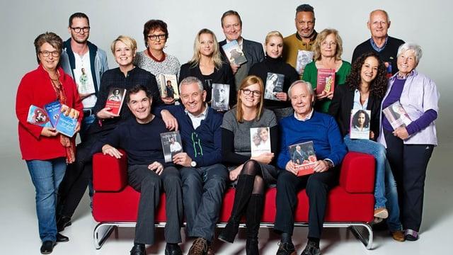 Verlegerin Gabriella Baumann-von Ark auf dem Sofa mit diversen Autorinnen und Autoren.