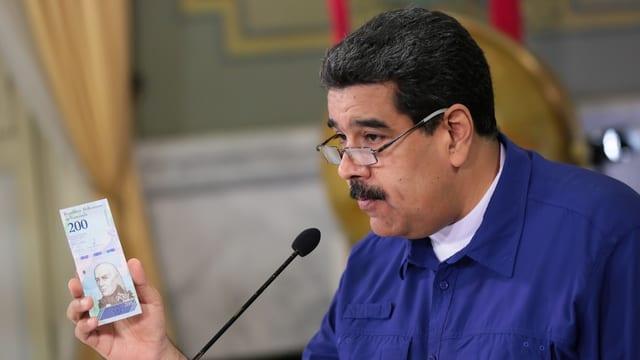 Maduro hält eine Banknote in der Hand