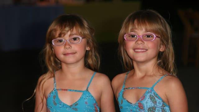 Eineiige Zwillingsmädchen tragen ihre Brillen.