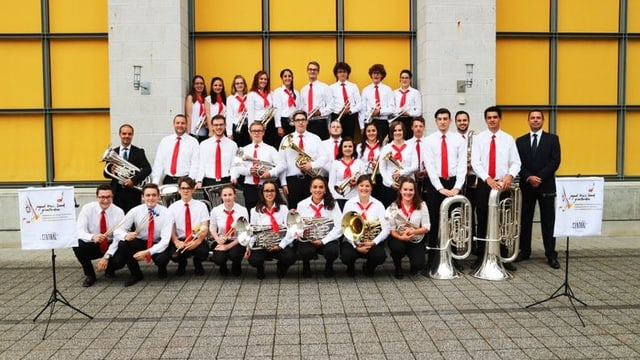 Musicistas e musicists cun lur dirigent da la Brass Band giuvanila dal Grischun.