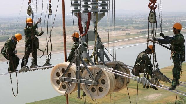 Symbolbild: Arbeiter montieren neue Kabel in luftiger Höhe auf einem Strommast.